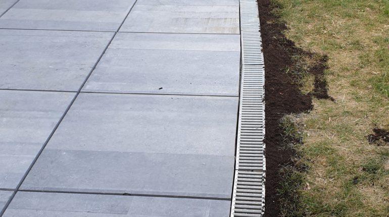 Création d'une terrasse en dalles de pierre bleue de 80x80cm par Greenrod, votre partenaire en entretien de jardins, élagage, construction d'abris de jardin etc.